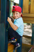 Little boy in cap climb up — Stock Photo