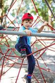 Little boy in cap climb on jungle gym — Stock Photo