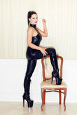 Woman step on chair in latex boots — Stock Photo