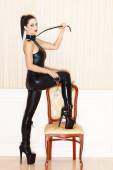 Woman in latex catsuit with whip and handcuffs — Stock Photo