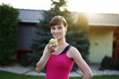 Young sporty woman eating green apple — Stock Photo