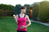 Hungry sporty woman with apple — Stock Photo
