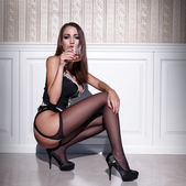 Sexy woman in corset and stockings squat with whiskey — Stock Photo