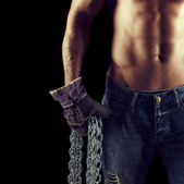 Sexy macho man holding chains in gloves — Foto de Stock