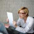 Blonde businesswoman reading letter — Stock Photo #61272605