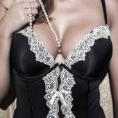 Sexy woman with big tits holding pearls — Stock Photo