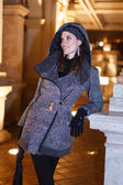Fashionable woman in long coat posing outdoor on corridor — Stockfoto