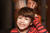 Little boys make mischief and showing donkey ears — Stock Photo