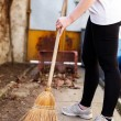 Woman sweeping on backyard — Stok fotoğraf #69064119