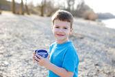 Petit garçon tenant l'eau propre dans la tasse en pointillé — Photo