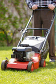 Senior man mowing grass — Stock Photo