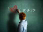 I love Literature. Schoolboy writing on a chalkboard. — Stock Photo