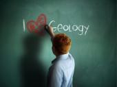 I love Geology. Schoolboy writing on a chalkboard. — Stock Photo