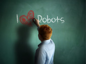 I love Robots. Schoolboy writing on a chalkboard. — Fotografia Stock