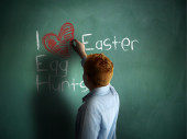 I love Easter Egg Hunts. Schoolboy writing on a chalkboard. — Stock Photo