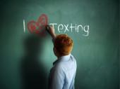 I love Texting. Schoolboy writing on a chalkboard. — Stockfoto