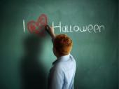 I love Halloween. Schoolboy writing on a chalkboard. — Stock Photo