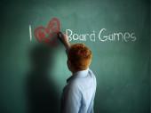 I love Board Games. Schoolboy writing on a chalkboard. — Stock Photo