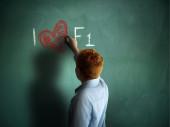 I love F1. Schoolboy writing on a chalkboard. — Foto de Stock