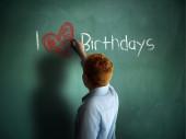 I love Birthdays. Schoolboy writing on a chalkboard. — Stock Photo