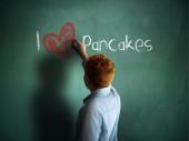I love Pancakes. Schoolboy writing on a chalkboard. — Stock fotografie