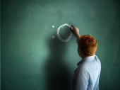 Surprised. Schoolboy drawing an emoticon on a chalkboard — Stock Photo