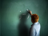 Wink. Schoolboy drawing an emoticon on a chalkboard — Stock Photo