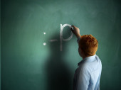 Sticking tongue out. Schoolboy drawing an emoticon on a chalkboard — Stock Photo