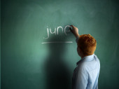 June. Schoolboy writing on a chalkboard. — Stock fotografie