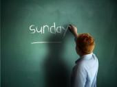 Sunday. Schoolboy writing on a chalkboard. — Stock Photo
