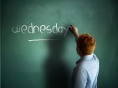 Wednesday. Schoolboy writing on a chalkboard. — 图库照片