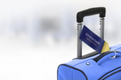 Amsterdam, Netherlands. Blue suitcase with label at airport. — Stock Photo