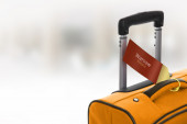 Warsaw, Poland. Orange suitcase with label at airport. — Stock Photo