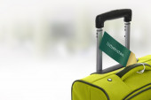 Uzbekistan. Green suitcase with label at airport. — Stock Photo