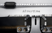"""Advertise"" written on an old typewriter — Стоковое фото"