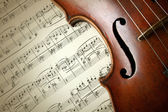 Detail of old scratched violin on music sheet — Zdjęcie stockowe