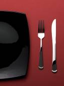 Silverware with black plate on red tablecloth — Zdjęcie stockowe