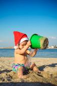 Baby in Santa Claus's cap is played on a beach — Stock Photo