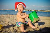 宝宝在圣诞老人的帽子打在沙滩上 — 图库照片