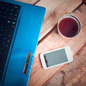 Laptop with mobile phone and coffee cup — Stok fotoğraf