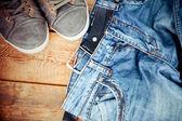 Schmutzige jeanshose ausgelöst stock mit ein paar turnschuhe — Stockfoto