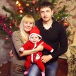 Happy young family with Christmas baby near the Christmas tree — Stock Photo #59984945
