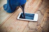 Scarpa tacco alto schiacciando un telefono cellulare. — Foto Stock