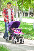 Father pushing a baby stroller — Stock Photo