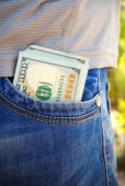 Hundred dollars which are sticking out from a pocket of jeans — Stock Photo