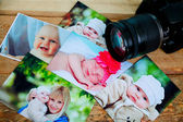 Children's photos and camera on a wooden background. — Stock Photo