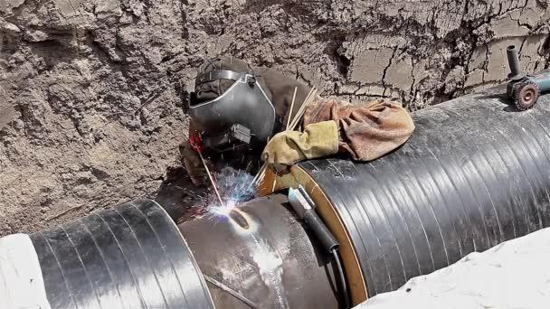 Welder is welding the pipeline in trench — Vidéo