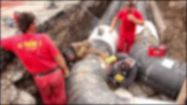 Blurred view on team of workers until assembly a new pipeline. — Stock Video
