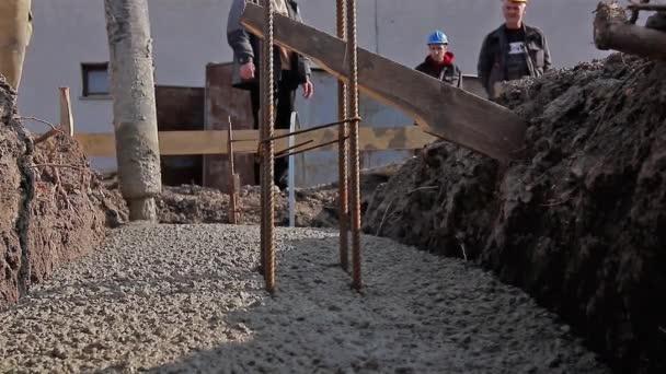 Hormigón se está extendiendo en la Fundación sobre barras de acero de refuerzo. — Vídeo de stock