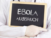 Doctor shows information: Ebola outbreak in german — Stock Photo